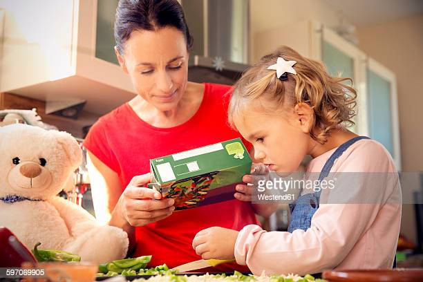 mother and daughter in kitchen preparing pizza - aliment surgelé photos et images de collection