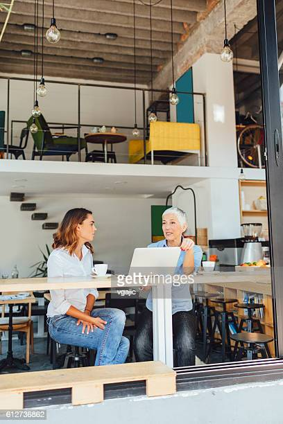 Mother and Daughter In Local Coffee Shop