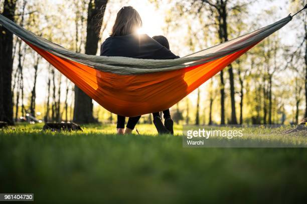 Mother and daughter in park relaxing in a hammock