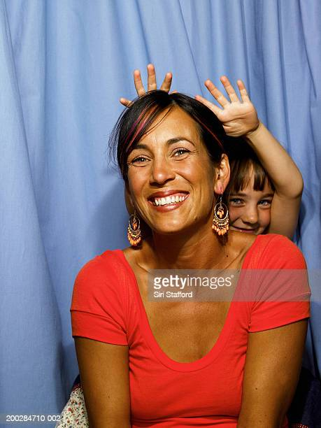 Mother and daughter (6-8) in photo booth, girl's hands on woman's head