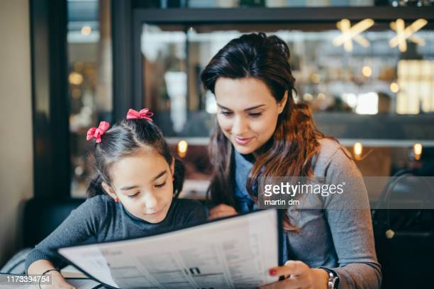 mother and daughter in restaurant - menu stock pictures, royalty-free photos & images
