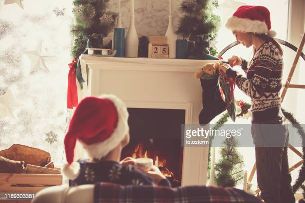 mother and daughter in santa's hats enjoying christmas day - christmas stocking stock pictures, royalty-free photos & images
