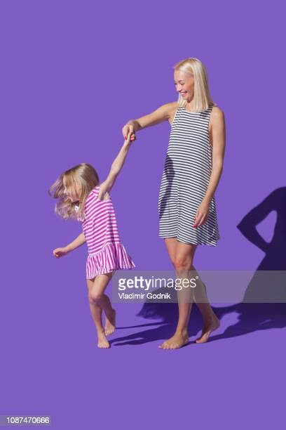 mother and daughter in striped dresses dancing on purple background - striped dress stock photos and pictures