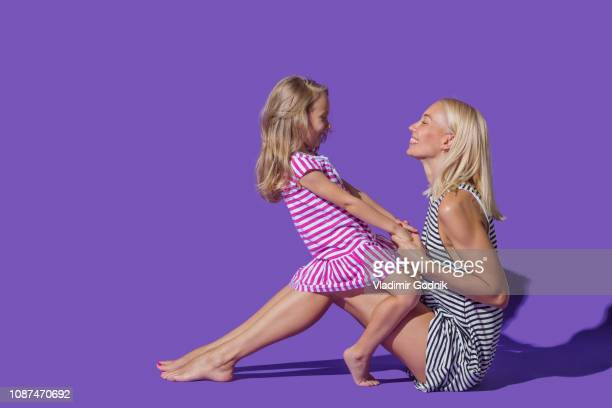 mother and daughter in striped dresses on purple background - girl strips stock pictures, royalty-free photos & images