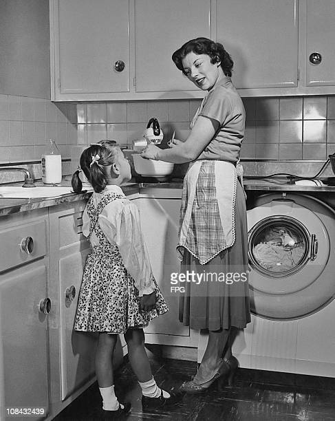 A mother and daughter in the kitchen using a food mixer circa 1950