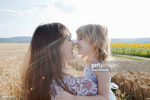 Mother and daughter in wheat field hugging