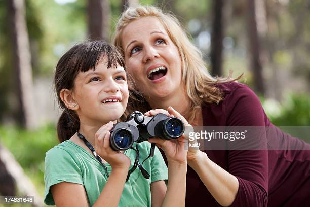 Mother and daughter in woods with binoculars