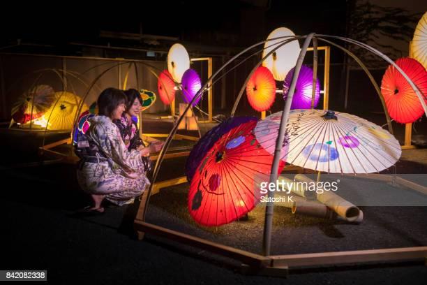 和傘で cadle ライトに座っている浴衣で母と娘 - 工芸品 ストックフォトと画像