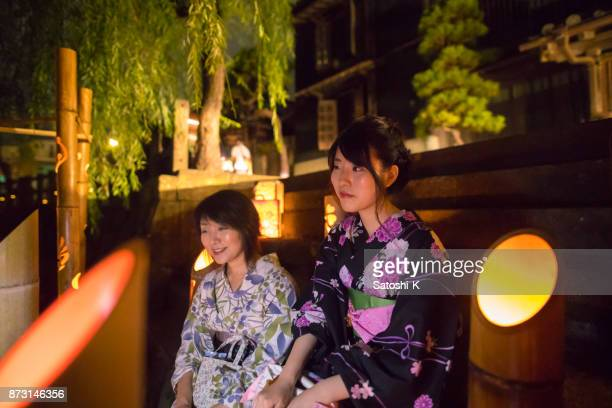 Mother and daughter in yukata sitting on stairs in bamboo lights