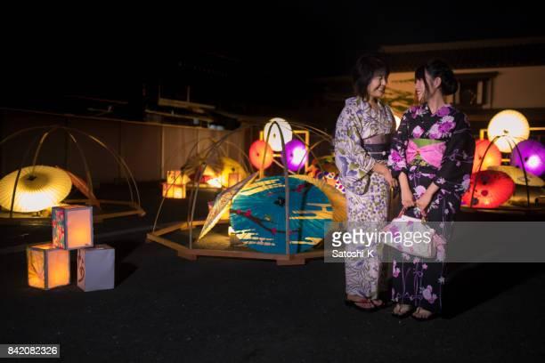 和傘とボックス cadle ライトで浴衣立ちで母と娘 - ボン ストックフォトと画像