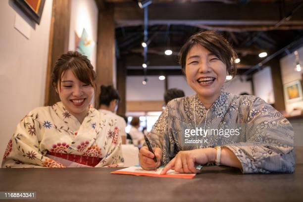 カフェで浴衣の母と娘がメッセージを書く - ボン ストックフォトと画像