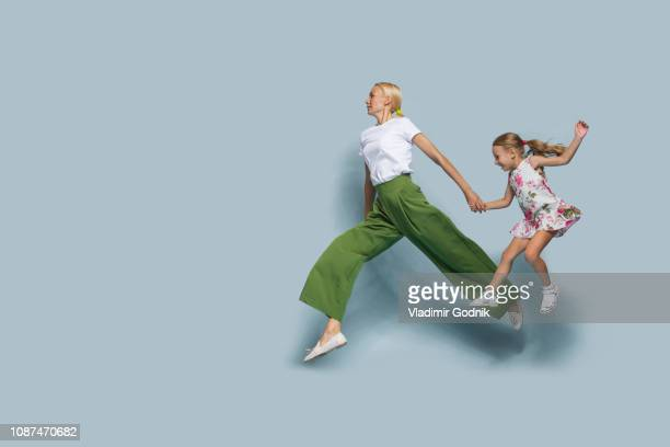 mother and daughter jumping against blue background - in de lucht zwevend stockfoto's en -beelden