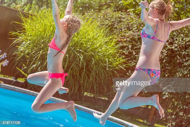 Mutter und Tochter beim Springen in Schwimmbad