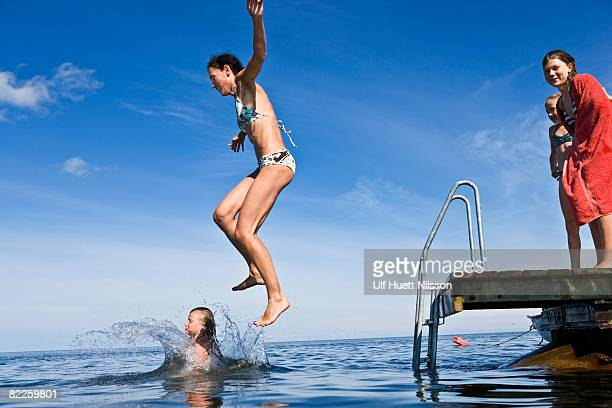 mother and daughter jumping into the ocean oland sweden. - sea swimming stock photos and pictures