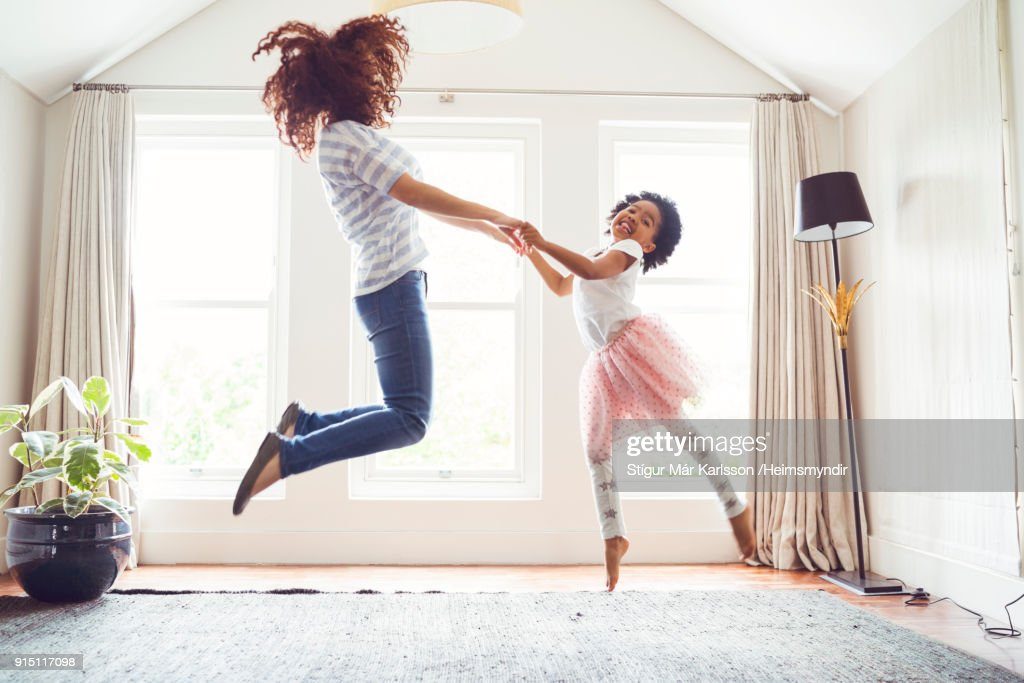 Mother and daughter jumping while doing ballet : Stock Photo
