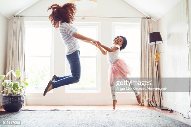 mother and daughter jumping while doing ballet - african american family home stock photos and pictures