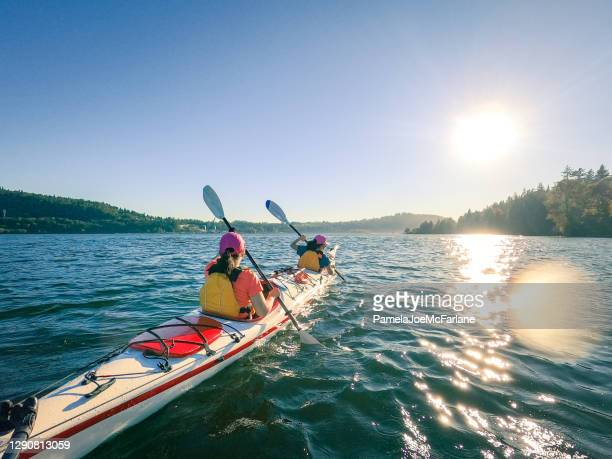 mother and daughter kayaking together, suburban neighborhood in background - vancouver canada stock pictures, royalty-free photos & images