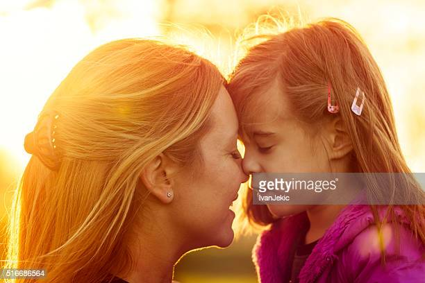 Mother and daughter kissing at sunset closeup