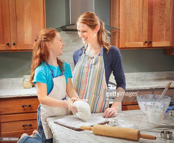 mother and daughter kneading dough / baking in home kitchen