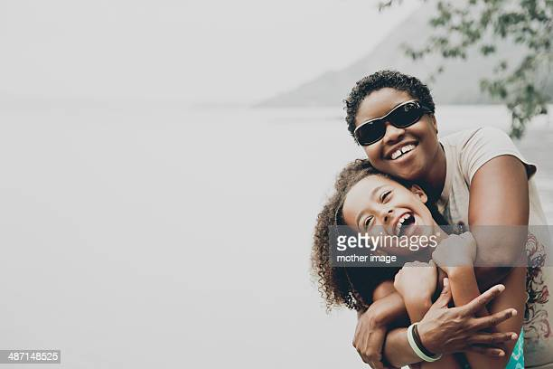 mother and daughter laughing and hugging - leanincollection stock pictures, royalty-free photos & images