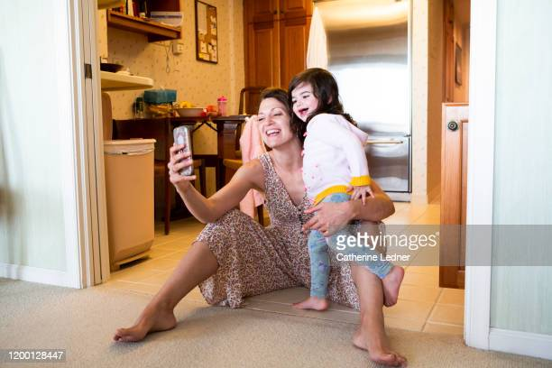 Mother and daughter laughing and smiling while face timing on kitchen floor