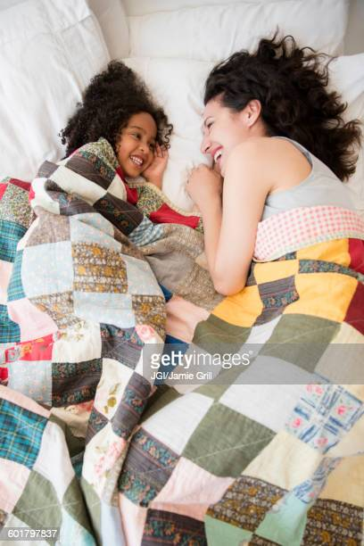 Mother and daughter laughing on bed