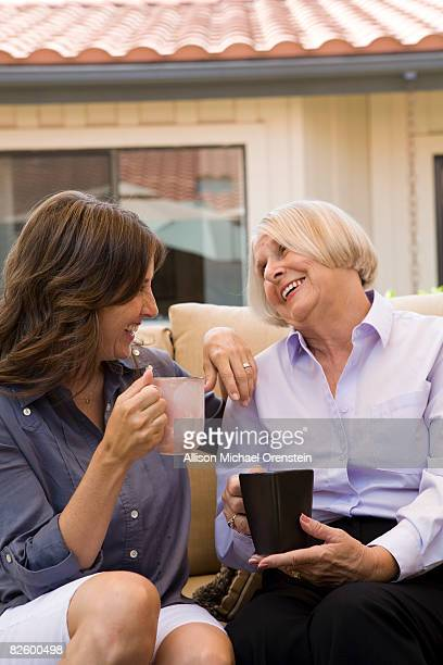 Mother and daughter laughing over a cup of coffee