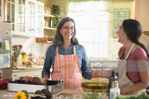 Mother and daughter laughing while cooking in domestic kitchen