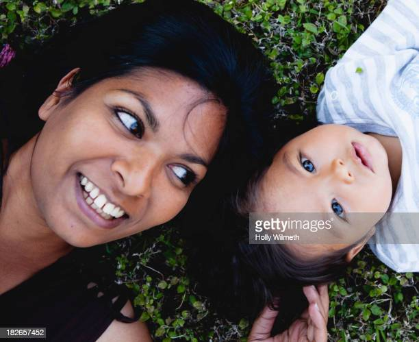 Mother and daughter laying in grass