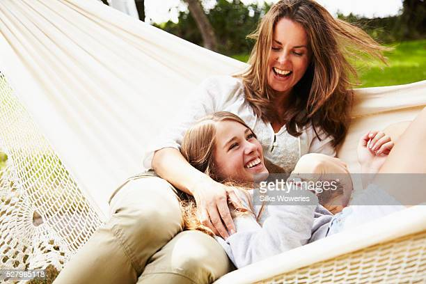 Mother and daughter (16-17) laying in hammock and having fun