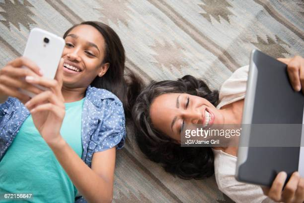 Mother and daughter laying on carpet using cell phone and digital tablet