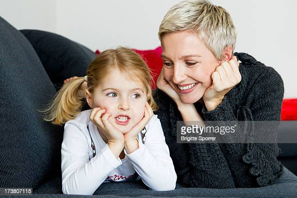 Mother and daughter laying on sofa