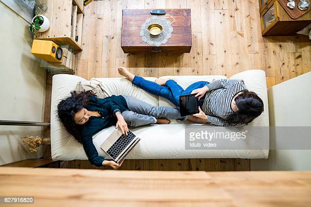 mother and daughter laying on the sofa using smart devices - convenience stock photos and pictures