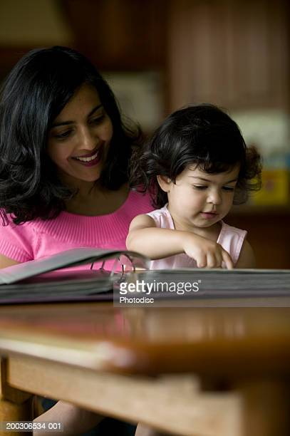 Mother and daughter (3-4) leafing through ring binder