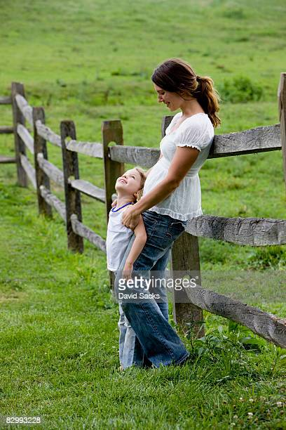 Mother and daughter leaning against fence