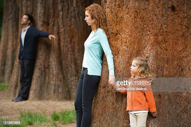 Mother and daughter leaning against tree, father standing separate in background