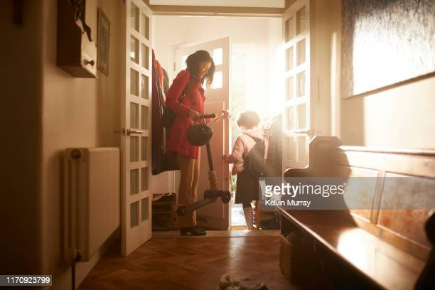 a mother and daughter leaving the house. - ochtend stockfoto's en -beelden