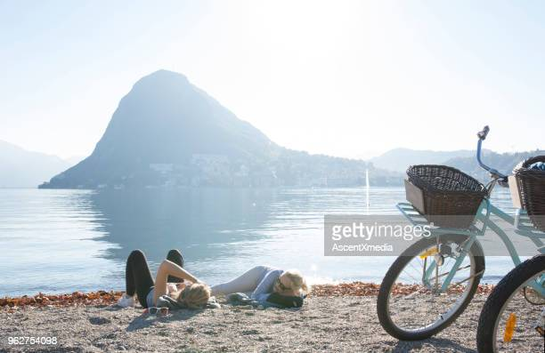 Mother and daughter lie on beach with bikes