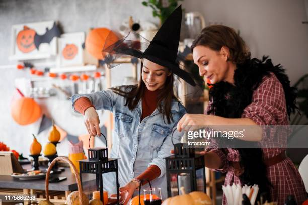 mother and daughter lighting candles in halloween decor - halloween decoration stock pictures, royalty-free photos & images