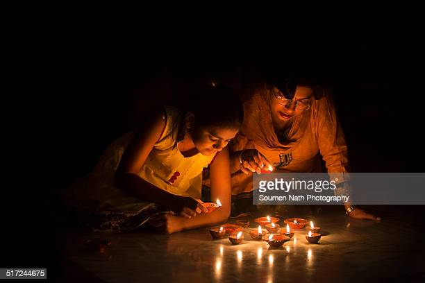Mother and daughter lighting diyas on Diwali