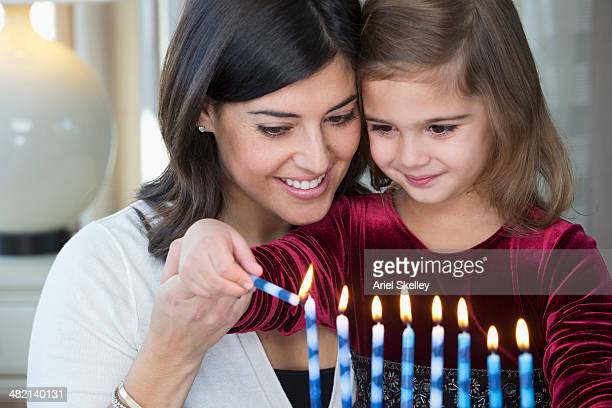 mother and daughter lighting hanukah menorah - hanukkah imagens e fotografias de stock