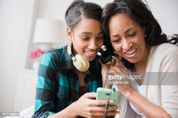 Mother and daughter listening to cell phone music on headphones