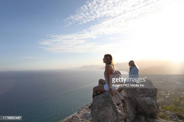 mother and daughter look off from rock summit - travel stock pictures, royalty-free photos & images