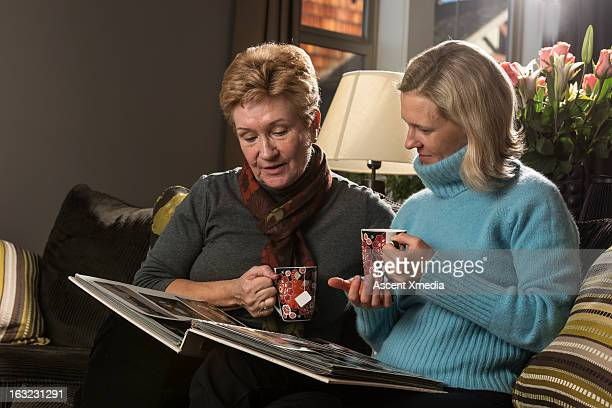 Mother and daughter look over photo album together
