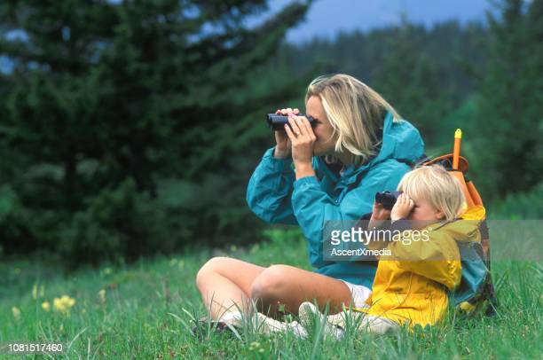 mother and daughter look through binoculars while sitting in meadow - jacket stock pictures, royalty-free photos & images