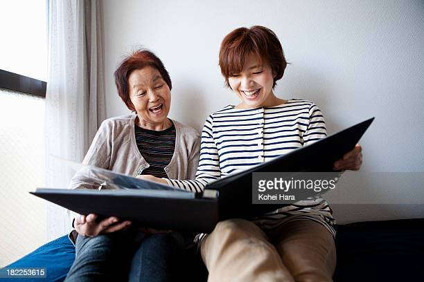 mother and daughter looking a photo album - two parents ストックフォトと画像