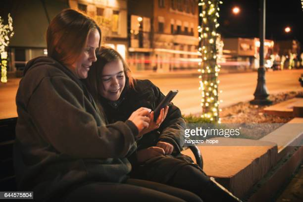 Mother and Daughter Looking at a Phone at Night