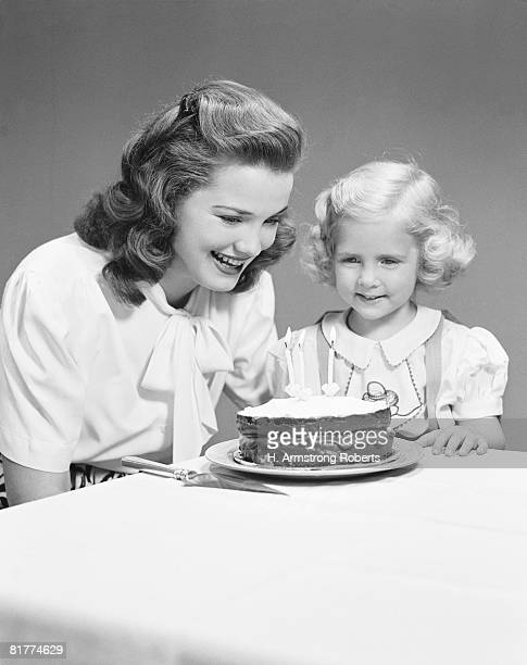 Mother and daughter looking at birthday cake with three candles on it, smiling.