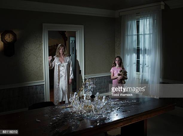 mother and daughter looking at broken chandelier