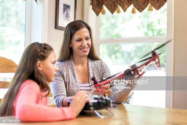 mother and daughter looking at drones for a science project - remote control helicopter stock photos and pictures